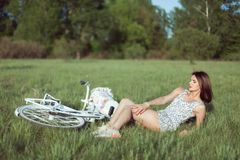 Young woman on a meadow with a bicycle. stock photography