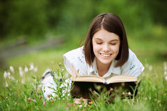 Young woman lies on grass and reads Royalty Free Stock Image