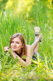 Young woman lies on green grass Stock Images