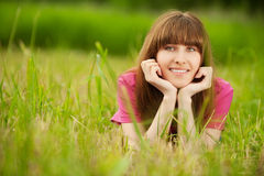 Young woman lies on green grass Stock Image