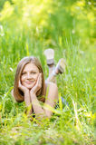 Young woman lies on green grass Royalty Free Stock Photography