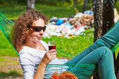 Young woman lies in hammock with glass of beverage. Young woman in dark sunglasses lies in hammock with glass of beverage, pile of garbage in background out of stock photos