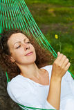 Young woman lies in hammock and looks at yellow flower. She holds in her hand stock image