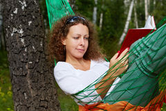 Young woman lies in hammock and reads book. Young woman lies in hammock suspended between two thick birches and reads book royalty free stock photo