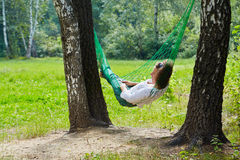 Young woman lies in hammock suspended between birches. Young woman lies in hammock suspended between two thick birches stock photo