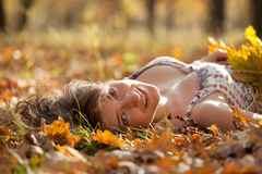 Young Woman Lies In Oak Leaves Stock Photos