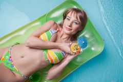 Young woman  lies  on an inflatable mattress Royalty Free Stock Image