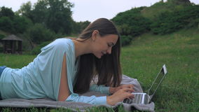 A young woman lies on lawn and gaining a message on the computer. Laughing, rejoicing. stock video footage
