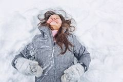 Young woman lies in a snowdrift and laughs royalty free stock photo