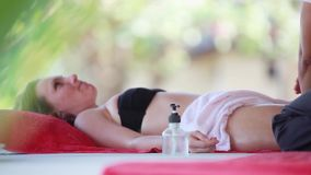 Young woman lies in spa saloon relaxing on the tropical beach. Massage therapist doing legs oil massage. 1920x1080. Beautiful woman lies in spa saloon on the stock video footage