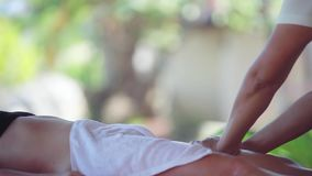 Young woman lies in spa saloon on the tropical beach. Massage therapist doing legs massage on blurred leaves bakground stock footage