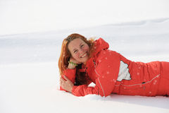 Young woman lies on to snow Royalty Free Stock Image
