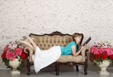 Young woman lies on vintage couch and reads book Stock Photos