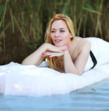 Young woman lies on a white water bed, relaxing outdoors on back Stock Image