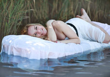 Young woman lies on a white water bed, relaxing outdoors Royalty Free Stock Photo