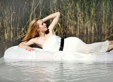 Young woman lies on a white water bed, relaxing outdoors Royalty Free Stock Images