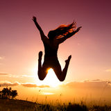 Young woman lifestyle. Young woman joyfully jumping with sunset in backround royalty free stock photos