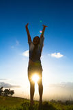 Young woman lifestyle. Young woman joyfully jumping with sunset in backround stock photo