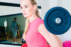 Young woman lifting a barbell in the gym Royalty Free Stock Photos