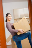 Young woman lifting cardboard box. Woman lifting cardboard box while moving home, smiling Royalty Free Stock Photography