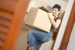 Young woman lifting cardboard box Stock Photos