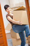 Young woman lifting cardboard box. Woman lifting cardboard box while moving home, smiling Stock Images
