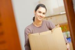 Young woman lifting cardboard box. Woman lifting cardboard box while moving home, smiling Royalty Free Stock Photo