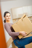Young woman lifting cardboard box. Woman lifting cardboard box while moving home, smiling Royalty Free Stock Images