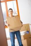 Young woman lifting cardboard box. Woman lifting cardboard box while moving home, smiling Stock Photos