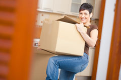 Young woman lifting cardboard box Royalty Free Stock Image