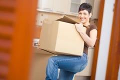 Young woman lifting cardboard box. Woman lifting cardboard box while moving home, smiling Royalty Free Stock Image