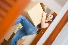 Young woman lifting cardboard box. Woman lifting cardboard box while moving home, smiling Stock Image
