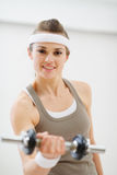 Young woman lifting dumb-bell in the gym Royalty Free Stock Photos