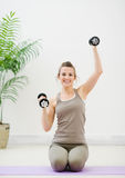 Young woman lifting dumb-bells Stock Photo