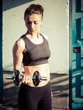 Young woman lifting a dumbbell outdoors Royalty Free Stock Photos