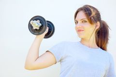 Young woman lifting dumbbell Stock Photo
