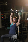 Young woman lifting the dumbbells Stock Image