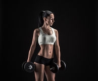 Young woman lifting the dumbbells Stock Photos