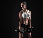 Young woman lifting the dumbbells. Fitness girl with dumbbells on a dark background Royalty Free Stock Photos