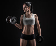 Young woman lifting the dumbbells Royalty Free Stock Images