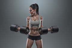 Young woman lifting the dumbbells Stock Images