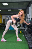 Young Woman Lifting Heavy Weight Exercise With Dumbbells on Broadest Muscle of Back at Gym