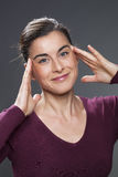 Young woman lifting her eyes for skin rejuvenation Stock Image