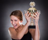 Young woman lifting trophy Royalty Free Stock Photo