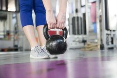 Young woman lifting weight in gym. Young woman lifting weight in the gym Royalty Free Stock Photography