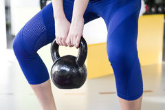 Young woman lifting weight in the gym. Young woman lifting the weight in the gym Royalty Free Stock Photography