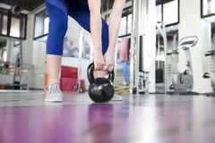 Young woman lifting weight in the gym. Young woman lifting weight in the modern gym Stock Photo