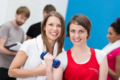 Young woman lifting weights aided by a friend Royalty Free Stock Photography