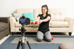 Young woman lifting weights on camera Stock Photography