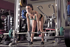 Young woman lifting weights. Picture of young woman making exercise at the gym stock photo